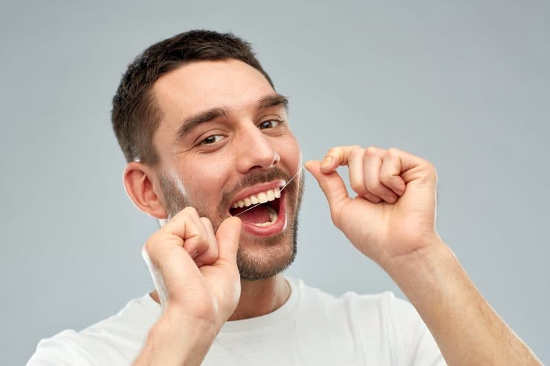 man with dental floss cleaning teeth